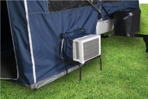 An AC unit attached to a tent that has an AC port on the wall